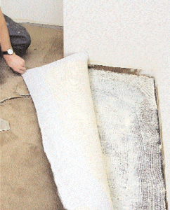 After the cushion has been installed, the carpet is cut 75 mm to 100 mm longer than the area measured. Carpet seams should be at a right angle to cushion seams, or offset at least 150 mm to either side. When gluing, the floor adhesive must be spread uniformly over the cushion, leaving ridges of sufficient height to achieve full and complete coverage of the cushion and carpet backing, including penetration into the backing's deepest recesses. To ensure the installation progresses properly, a small area should be selected to confirm the amount and placement of adhesive. Here, the carpet is lifted so the installer can verify adhesive transfer and coverage into the backstitch of carpet.